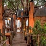 The entrance of a lodge with Masai style thatch and mud huts in Kenya