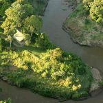 An aerial view of a safari tent surrounded by a winding river