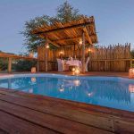 Swimming pool with thatch awning and lanters at night
