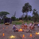 People in chairs around a fire