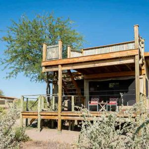 A double story guest chalet made of wood at Kalahari Plains