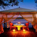 a table for two under an awning on a river bank at night