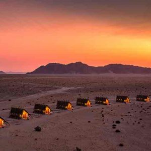 a row of small huts in a desert landscape at dusk