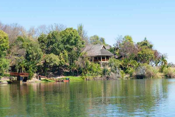 a lodge set on the banks of a river surrounded by trees