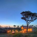 A safari tent in teh bush lit up with lanterns at night