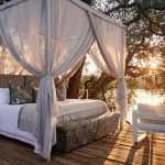 Double bed covered with mosquito net star bed at Victoria Falls Island Treehouse