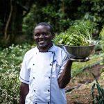 A man walking through a vegetable garden at Clouds Mountain Gorilla Lodge