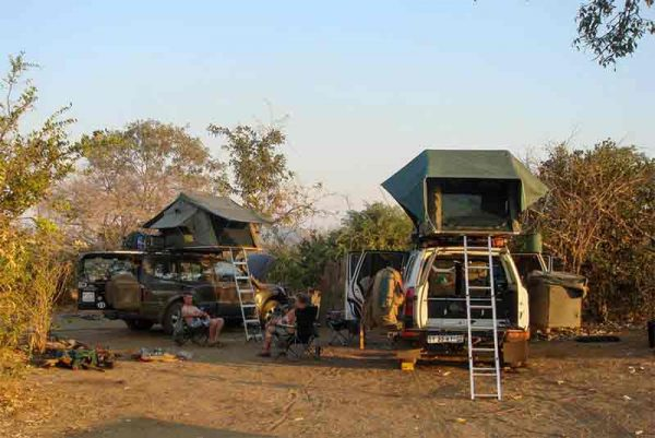 Several vehicles with roof top tents parked in the bush