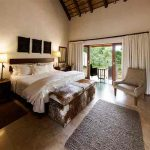 A room with double bed and views out to the African bush