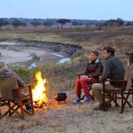 Guests sit in chairs on a river bank in front of a fire