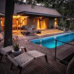 A swimming pool with wrap around wooden deck at Chitabe