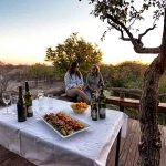two people sit on a deck talking with a table laid with snacks that looks out over the bush