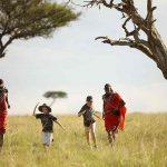 Masai tribesmen with children in the grass of Kenya
