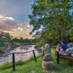 People relaxing on a couch overlooking the Mara River