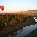 A hot air balloon flying over the Mara River
