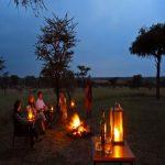 People enjoying drinks around a fire
