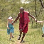 Children running and playing with Masai