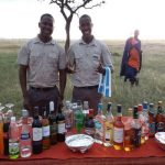 Ubuntu Camp staff in front of drinks tabel with Masai locals in the background