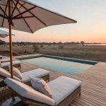 Luxury safari at pool edge with Mana pools sunset in the background